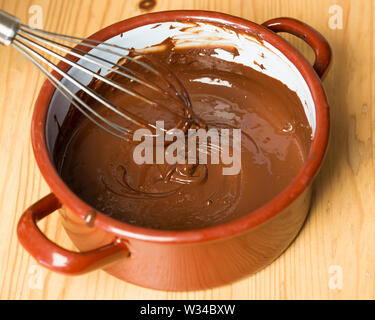 Pot with whisk and melted chocolate on wooden board - Stock Photo
