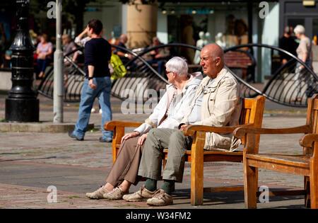 Dundee, Tayside, Scotland, UK. 12th July, 2019. UK weather: An elderly couple sitting on the summer seats enjoying the glorious weather in Dundee, UK - Stock Photo