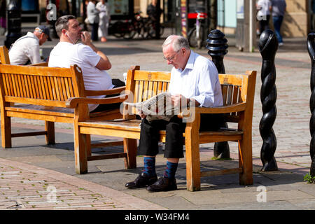 Dundee, Tayside, Scotland, UK. 12th July, 2019. UK weather: An elderly man sitting on the summer seats reading the Courier Newspaper in Dundee, UK - Stock Photo
