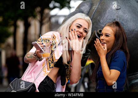 Dundee, Tayside, Scotland, UK. 12th July, 2019. UK weather: Two female friends standing together having fun beside the Desperate Dan statue in Dundee. - Stock Photo
