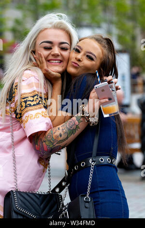 Dundee, Tayside, Scotland, UK. 12th July, 2019. UK weather: Two female friends standing hugging eachother beside the Desperate Dan statue in Dundee - Stock Photo
