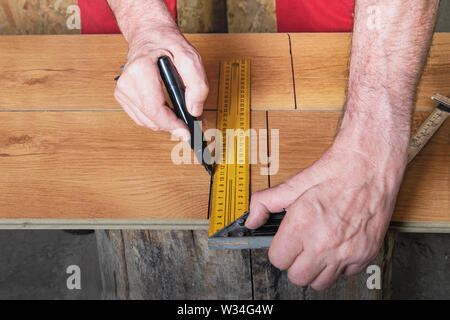 Hands of the worker mark a laminate with the help of a ruler, a square and a felt-tip pen. The master worker in the red jumpsuit prepares the laminate - Stock Photo