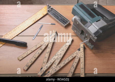 Electric jigsaw, folding ruler, square, marker for marking, replaceable files for electric saws lie on a wooden laminate. Tools carpenter and electric - Stock Photo
