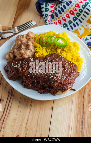 Mexican mole poblano chicken with rice and refried pinto beans - Stock Photo