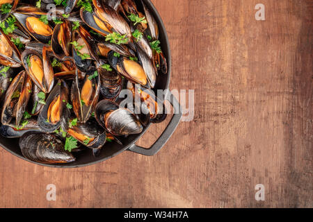 Marinara mussels cooked in a cooking pan, on a dark rustic background with a place for text, overhead close-up shot - Stock Photo
