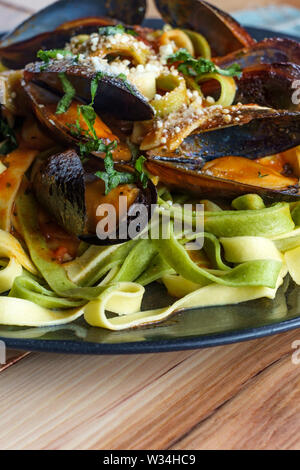 Seafood shell-on mussels marinara Italian seafood dish with tagliatelle pasta - Stock Photo