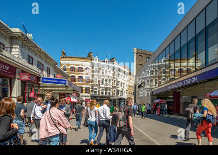 Farringdon Road busy with commuters and workers pouring out of Farringdon underground station on a sunny day - Stock Photo
