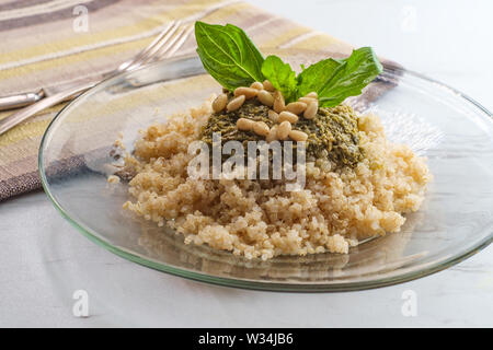 Healthy pesto quinoa salad with basil and pine nut garnish - Stock Photo