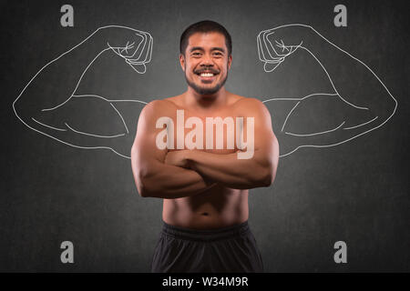 Smiling asian man with muscular upper body in front of muscle arms background. Fitness, workout and training concept. - Stock Photo