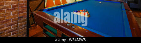 Retro blue pool table and billiard balls set up in restaurant with chairs and brick wall wide angle close up view - Stock Photo