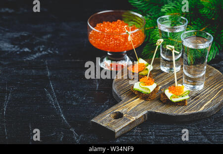 Delicious canapes with red caviar and two shots of vodka. - Stock Photo