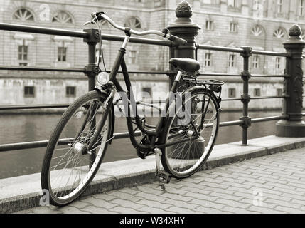 parked bicycles on the banks of the River Spree in downtown Berlin - Stock Photo