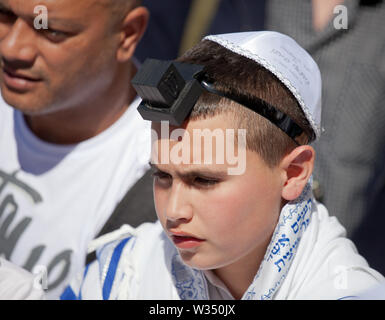 JERUSALEM, ISRAEL - Feb 18, 2013: Bar Mitzvah ritual at the Wailing wall in Jerusalem. A 13 years old boy who has become Bar Mitzvah is morally and et - Stock Photo