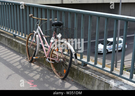 parked broken bicycle on a bridge in Berlin - Stock Photo