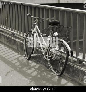 parked broken bicycle on a bridge in Berlin - Stock Photo