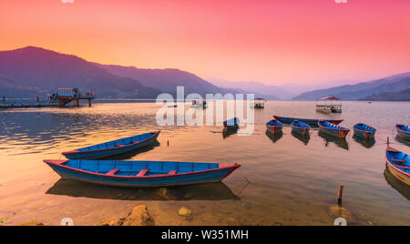 Different color Boats parked in Phewa Lake after sunset. Pokhara nepal. - Stock Photo