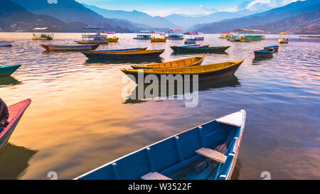 Different color Boats parked in Phewa Lake Sunset on background Pokhara Nepal. - Stock Photo