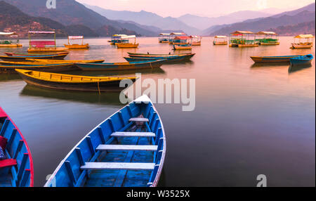 Different color Boats parked in Phewa Lake Sunset on background.Pokhara Nepal - Stock Photo