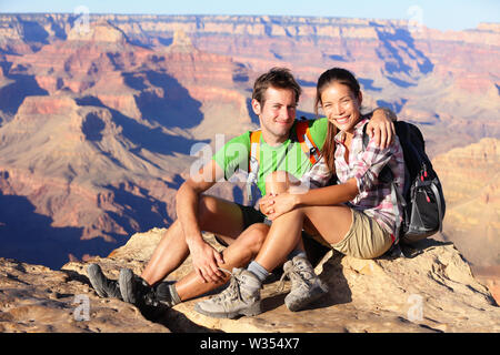 Hiking couple portrait - hikers in Grand Canyon enjoying view of nature landscape looking at camera smiling happy. Young couple trekking, relaxing after hike on south rim of Grand Canyon, Arizona, USA - Stock Photo
