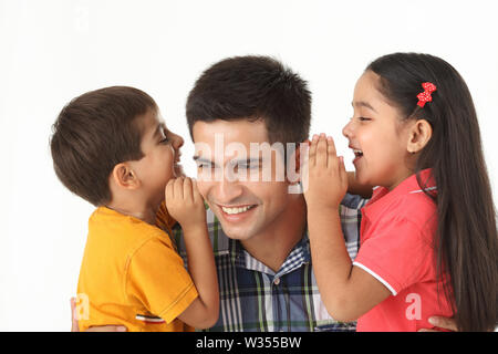 Boy and girl whispering into their father,s ear