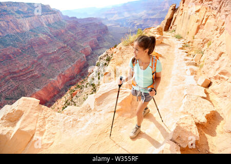 Hiker woman hiking in Grand Canyon walking with hiking poles. Healthy active lifestyle image of hiking young multiracial female hiker in Grand Canyon, South Rim, Arizona, USA. - Stock Photo