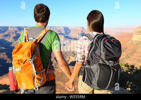 Couple holding hands looking at Grand Canyon. Romantic hikers enjoying view and romance while hiking Grand Canyon, USA. - Stock Photo