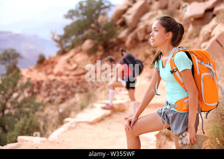 Hiker in Grand Canyon. Hiking woman and man resting tired enjoying hike and view on South Kaibab Trail, south rim of Grand Canyon, Arizona, USA. - Stock Photo