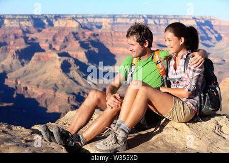 Hiking couple portrait - hikers in Grand Canyon enjoying view of nature landscape smiling happy. Young couple trekking, relaxing after hike on south rim of Grand Canyon, Arizona, USA. Man and woman. - Stock Photo
