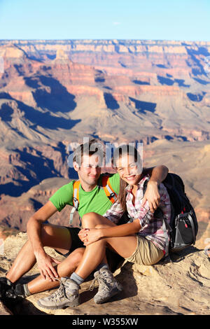 Hikers in Grand Canyon - Hiking couple portrait. Hiker man and woman enjoying view of nature landscape looking at camera smiling happy. Young couple relaxing after hike in Grand Canyon, Arizona, USA - Stock Photo