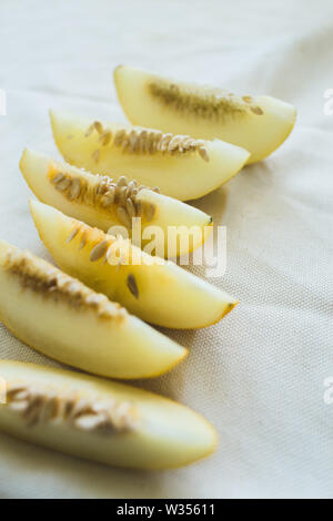 A group of brightly lit melon slices. seasonal summer fruits - Stock Photo