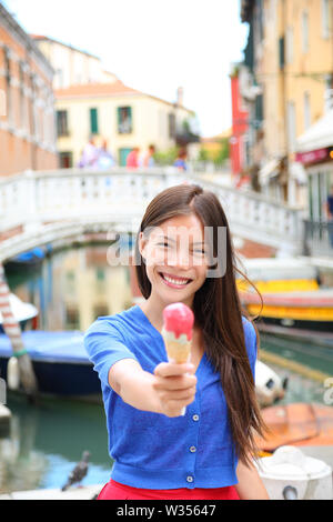 Ice cream eating woman in Venice, Italy on vacation travel showing gelato ice cream cone smiling happy looking at camera. Tourist having fun eating italian food on holidays in Venice, Italy, Europe. - Stock Photo