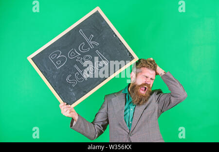 Teacher with tousled hair stressful about school year beginning. Teacher bearded man holds blackboard with inscription back to school green background. Keep working. Teaching stressful occupation. - Stock Photo