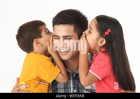 Indian boy and girl whispering into their father's ear - Stock Photo