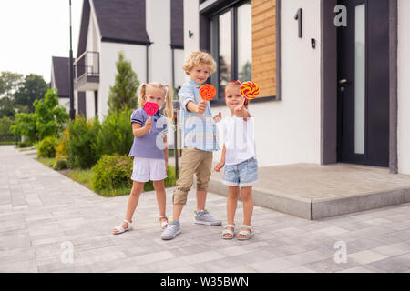 Delicious sweets. Cute pleasant kids showing you their lollipops while standing in front of the house - Stock Photo