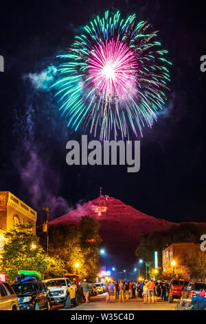 People watch Fourth of July fireworks on 'S' Mountain viewed from the main street in Salida, Colorado, USA - Stock Photo