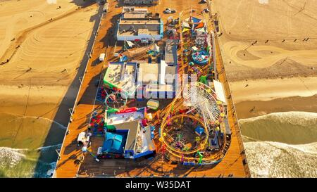 An aerial wide shot of an attraction park on a wooden pier at the beach - Stock Photo