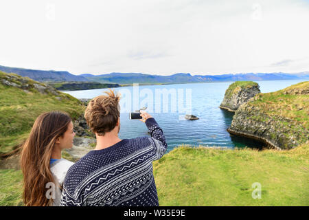Tourists on travel taking photo with smartphone on Iceland. Happy couple sightseeing taking pictures using smart phone visiting Arnarstapi, Snaefellsnes, Iceland.