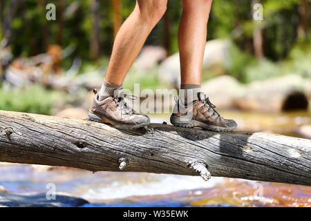 Hiking man crossing river in walking in balance on fallen tree trunk in nature landscape. Closeup of male hiker trekking shoes outdoors in forest balancing on tree. Balance challenge concept. - Stock Photo
