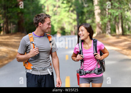 Happy couple of hikers hiking talking together, cheerful and fresh. Young active multiracial couple in outdoor activity hike in Yosemite National Park, California, USA. Asian woman, Caucasian man. Stock Photo