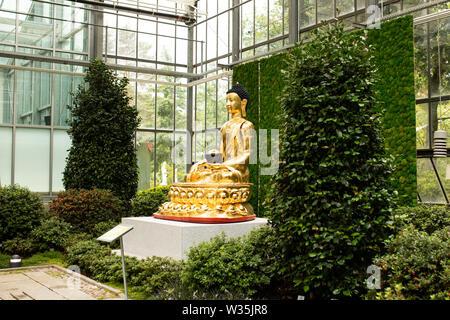 The golden Buddha statue in the indoor Japanese garden at botanika in Bremen, Germany. - Stock Photo