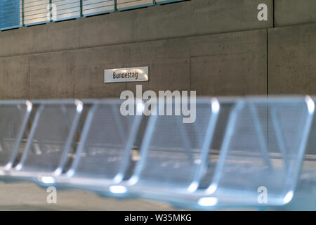 unfamiliar perspective with blurry metal seats in the foreground  at the Berlin undergroundstation Bundestag - Stock Photo