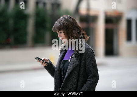 Young female using mobile phone app and waiting for a rideshare or pedestrian tourist checking online map for gps navigation.  Depicts city life and h - Stock Photo