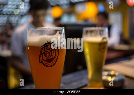 Two glasses of beer at the microbrewery Toit in Bangalore, India. - Stock Photo