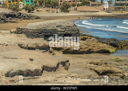 Panoramic view of the south coast of El Medano. Old military bunker in the middle and sand beach with people bathing in the background. Tenerife, Cana - Stock Photo
