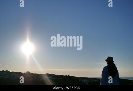 A brunette girl with a hat standing against the sky is looking at the sunrise - Stock Photo
