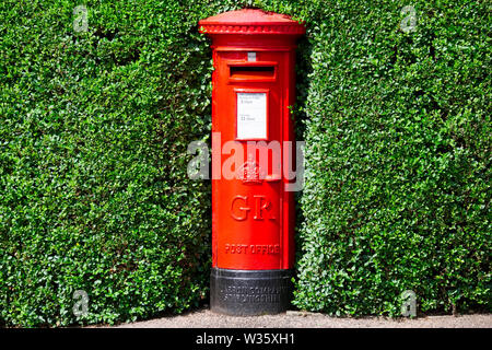 London, England / UK - July 13th 2019: Royal Mail red pillar postbox hidden in green hedge bush - Stock Photo