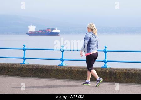 Greenock, Inverclyde / Scotland - July 11th 2019: Woman running as healthy active lifestyle at sea coast esplanade path - Stock Photo