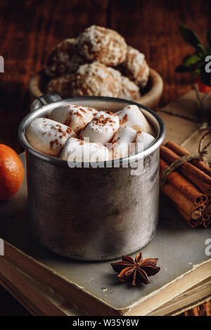 Metal mug of hot chocolate with marshmallows in rustic setting - Stock Photo