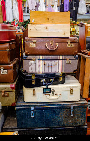 A stack of old and vintage suitcases, steamer trunks and wooden boxes on display for sell at charity recycling centre - Stock Photo