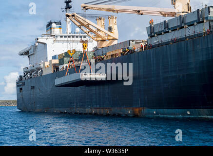 190710-N-LN093-1062   APRA HARBOR, Guam (July 10, 2019) Sailors assigned to Navy Cargo Handling Battalion (NCHB) 1, NCHB 5, and NCHB 13 maneuver a docking module for the Improved Navy Lighterage System (INLS) over the side of the Military Sealift Command maritime prepositioning force ship USNS 2nd Lt. John P. Bobo (T-AK 3008). The integration of active and reserve Navy Cargo Handling Battalions, Naval Beach Group 1, and Maritime Prepositioning Ships Squadron (MPSRON) 3 for INLS Lift on Lift Off (LOLO) increases Maritime Prepositioning Force (MPF) interoperability, proficiency and theater famil - Stock Photo